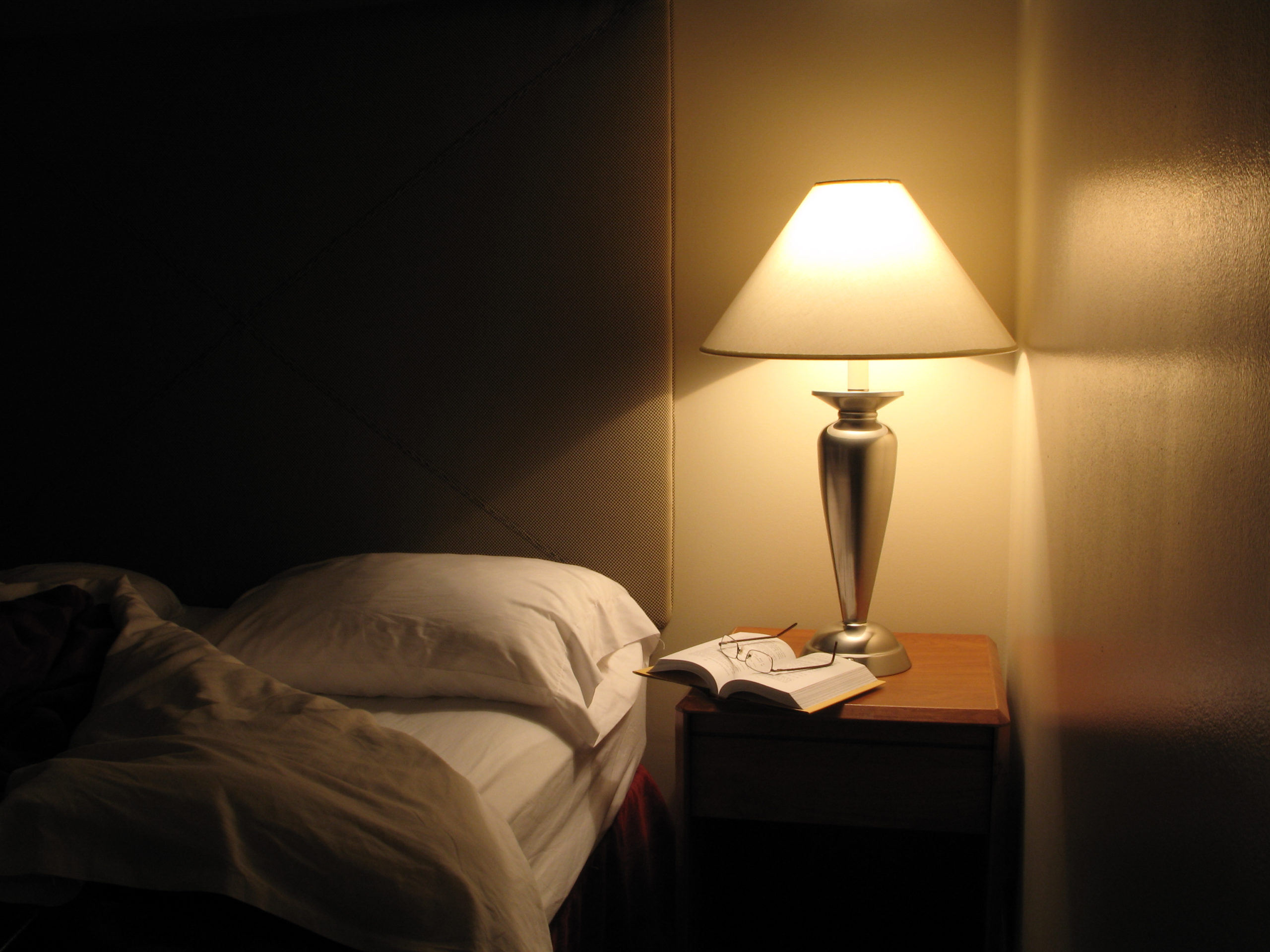 Night scene in hotel room, nightstand with lamp, bed turned down, opened book and reading glasses. 1st in series. Great wall reflection and texture.