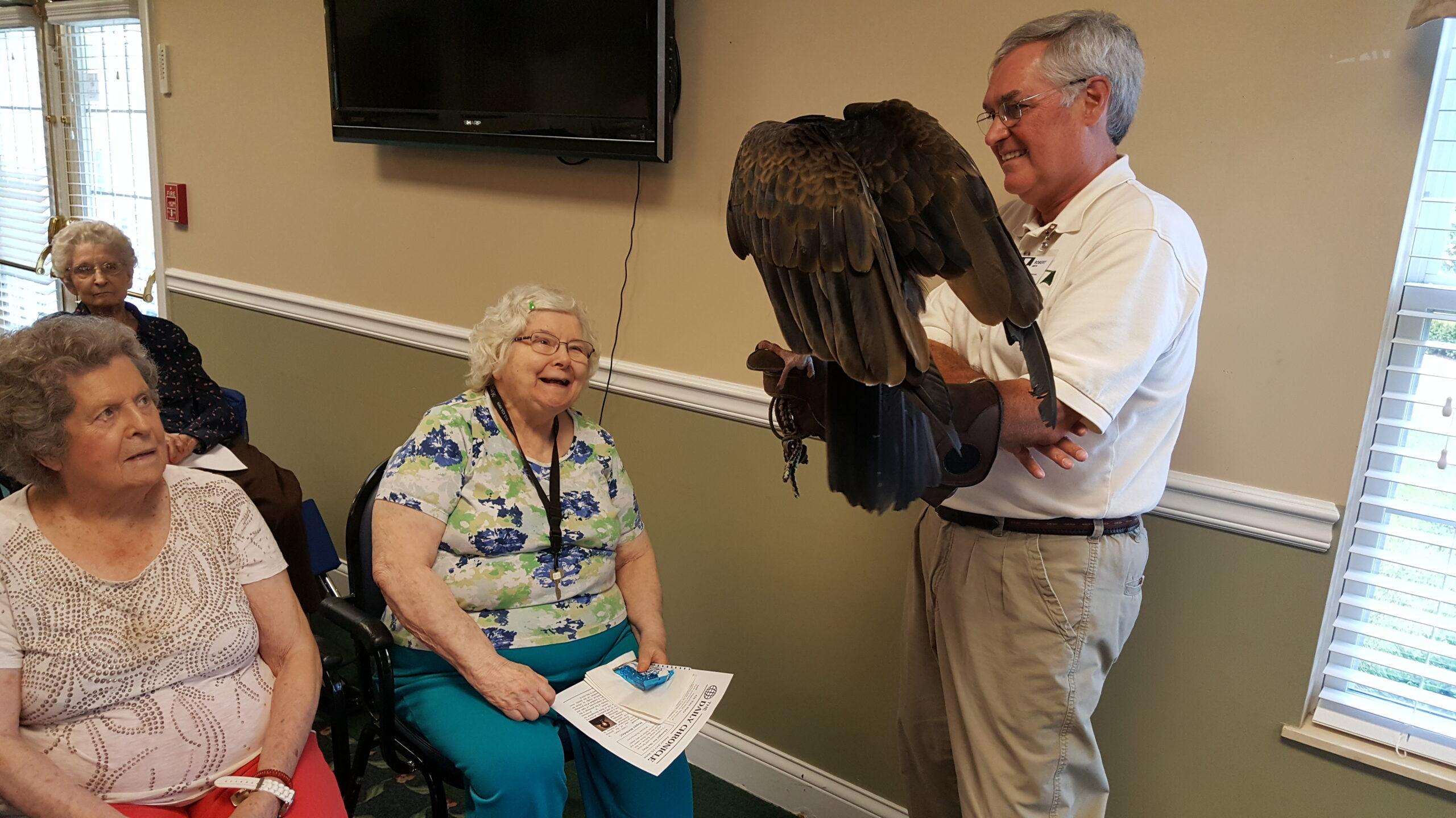 Residents Juanita Hume and Barbara Vorpe meet Earl the Vulture as Robert holds him