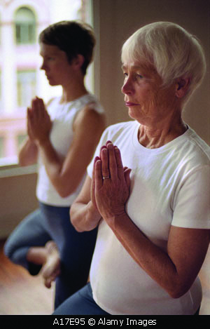 A17E95 Two women a mother and daughter practicing yoga together